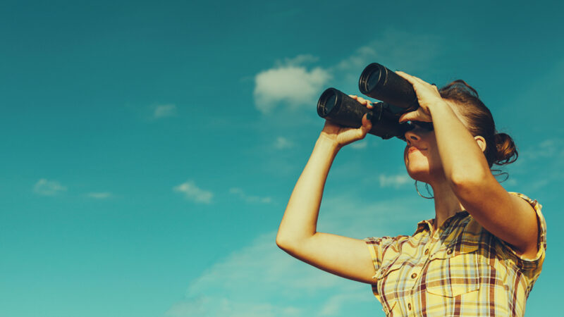 A young person looking through binoculars with a sky blue background.